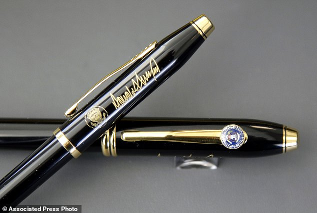 In this Tuesday, Feb. 14, 2017, photo A.T. Cross Co. custom-made pens, designed for President Donald Trump, featuring his signature and presidential seals, are displayed together at the Cross Company Store in Providence, R.I. Trump chose the Cross Century II model, top, for deliveries to the White House over the Cross Townsend model, below. (AP Photo/Steven Senne)